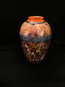 """Desert Urn"" is the title of this 81/2"" tall x 51/2"" diameter hollow vessel I turned. It combines silver inlay into the pernambuco and ebony rim at the top.  I gilded the lower body of the vessel with silver leaf and did a patina finish over it."